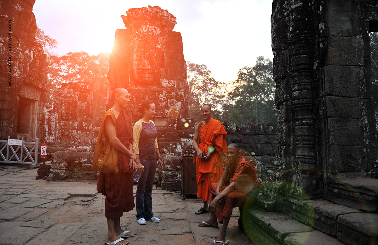 Female tourist is talking to Buddhist monks in Bayon Temple.
